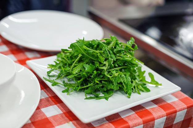 白い正方形板に新鮮なルッコラのサラダ Premium写真