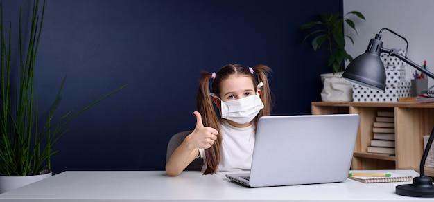 Дистанционное обучение онлайн-образование. школьница в медицинской маске учиться на дому, работать на ноутбуке ноутбука и делать домашнее задание в школе. карантин коронавируса. Premium Фотографии