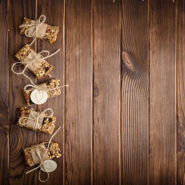 自家製グラノーラオートミールエネルギーバー、健康的なスナック、木製テーブル、トップビュー Premium写真