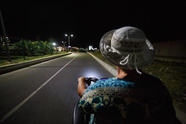公園で夏の夕日を楽しむエレガントな成熟した女性 Premium写真