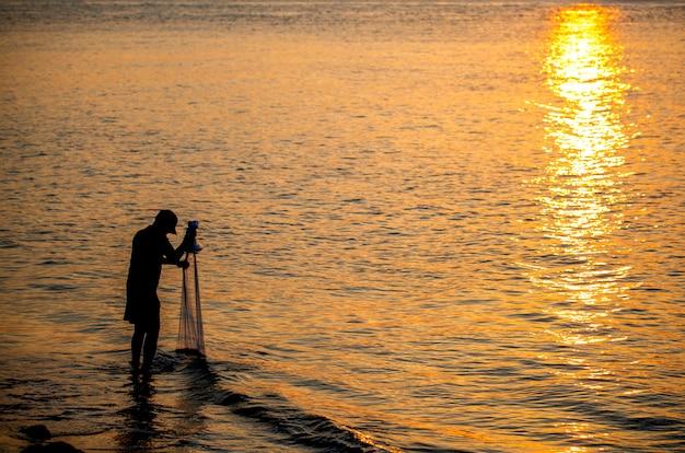 Рыбак забрасывает сеть морем утром, на рассвете Premium Фотографии