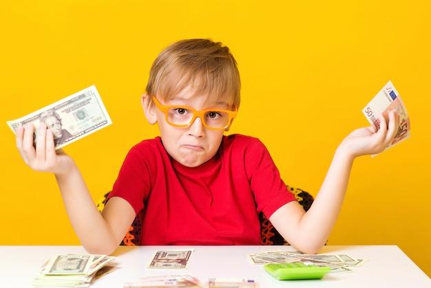 お金を保持していると新しいビジネスを考えて小さな男の子が起動します。黄色の背景の上の現金で眼鏡の小さな教授 Premium写真