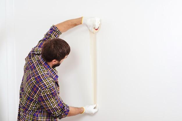 Ремонт дома. маляр с помощью маскирующей ленты перед покраской. художник человек за работой. Premium Фотографии