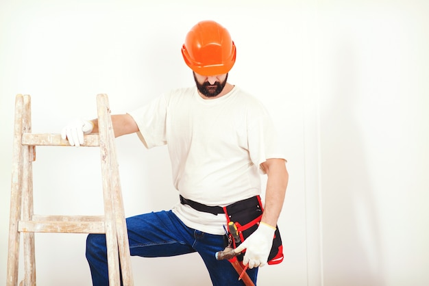 Ремонт дома. художник человек за работой. разнорабочий с поясом для инструментов. Premium Фотографии