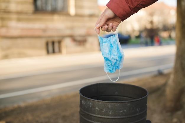 女性は屋外のゴミ箱に医療用マスクを投げます。使用済みのフェイスマスクはゴミ箱に捨てられます。マスクは常に家の外に出てください。 Premium写真
