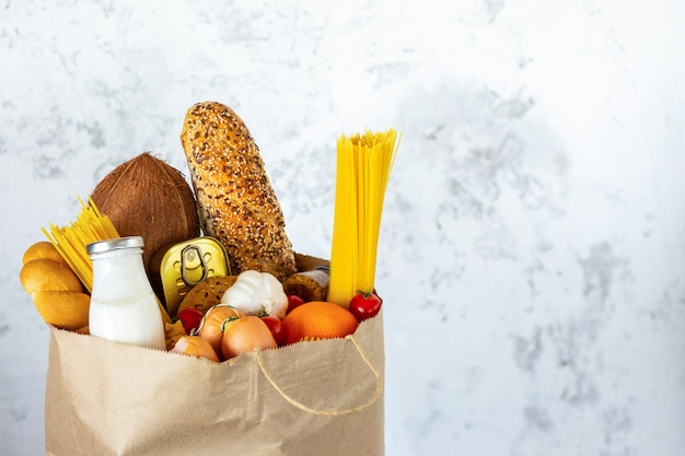 Полный бумажный мешок со здоровой пищей. здоровая пища фон. концепция продовольственного супермаркета. молоко, сыр, хлеб, фрукты, овощи, авокадо, ананас и спагетти. покупки в супермаркете. доставка на дом Premium Фотографии