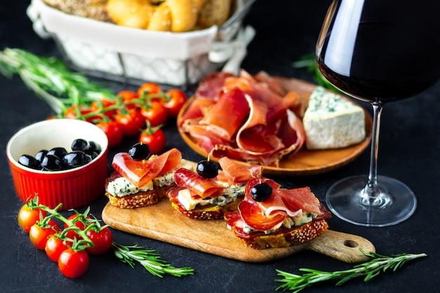 赤ワインは、黒い背景にベルチーズ、ハモン、生ハム、オリーブに注がれます。木の板にワインのおやつ。チーズとワインのスナックを添えたパン。パーティーの美味しいおやつ。 Premium写真