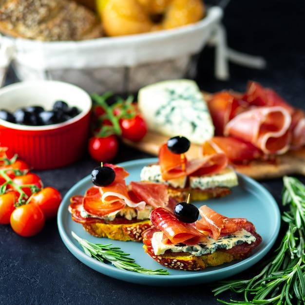 Винная закуска на деревянной доске. белое вино, сыр, хамон, прошутто, с салями и оливками на черном фоне. свежеиспеченный хлеб с сыром и винными закусками. вкусные закуски к вечеринке Premium Фотографии