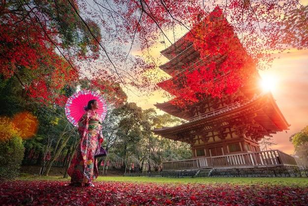 着物の伝統的な衣装で日本人の女の子が公園を散歩します。 Premium写真