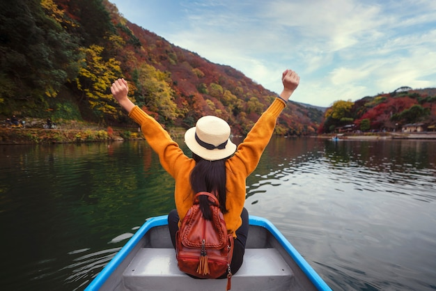 アジアの女の子は嵐山公園の川でパドルとレンタルボートでリラックスします。 Premium写真