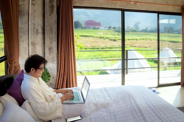 Деловой человек расслабиться и работать на компьютере в спальне Premium Фотографии