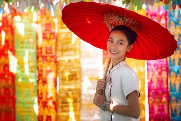 Азиатская девушка в северном традиционном костюме и красный зонт Premium Фотографии