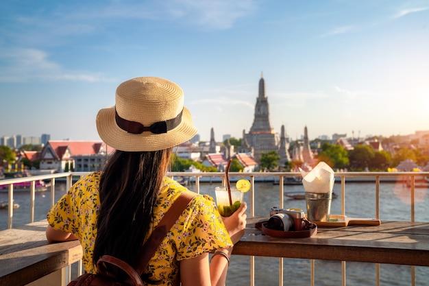 座っているアジアの女の子とワットアルン寺院の背景を持つワットでリラックス Premium写真