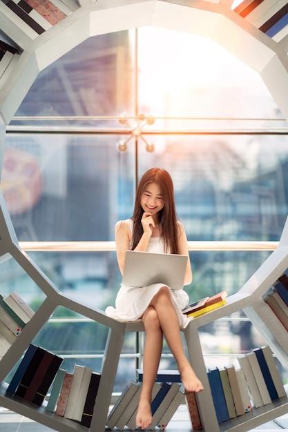 Азиатская студентка прочитала учебник в библиотеке своего университета Premium Фотографии