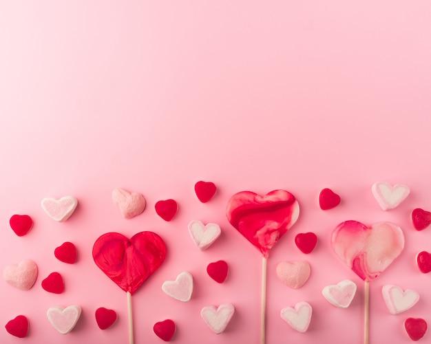 ハート型の甘いお菓子とピンクのロマンチックな休日の背景。テキスト用のスペースを持つ聖バレンタインの装飾的なカード。愛のテーマ。 Premium写真