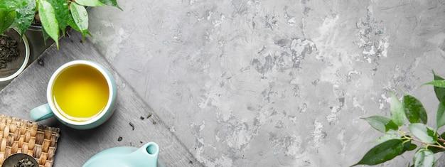 灰色のコンクリートの背景に青いカップで緑茶のカップ。 Premium写真