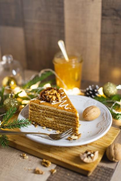 レーズンとナッツの木製テーブルの上のサワークリームと自家製蜂蜜ケーキ Premium写真
