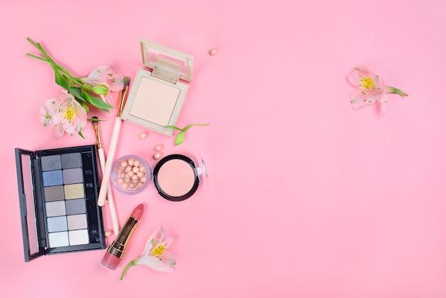 ピンクの背景の化粧ブラシで装飾的な化粧品のセット Premium写真