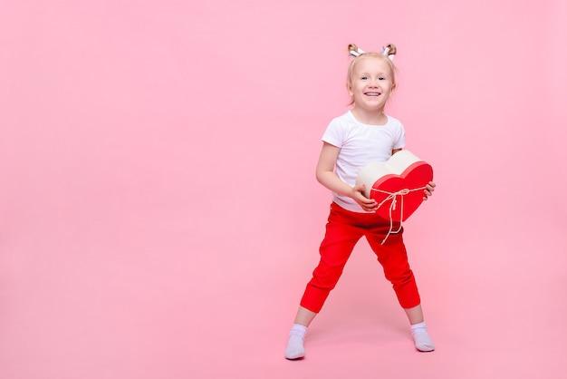 Смешная девочка в белой футболке и красных штанах с коробкой в форме сердца на розовом фоне. детский портрет с пространством для текста. Premium Фотографии