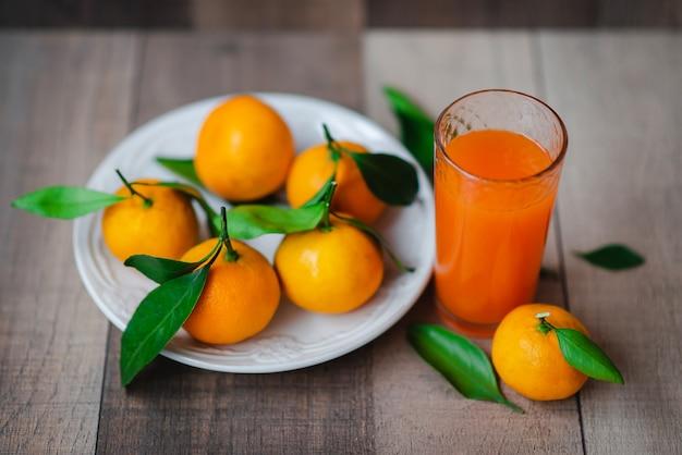 Цитрусовый сок и свежий мандарин Premium Фотографии