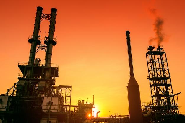 オレンジ色の空の夕焼け、石油およびガス産業プラントの石油化学産業の煙突 Premium写真