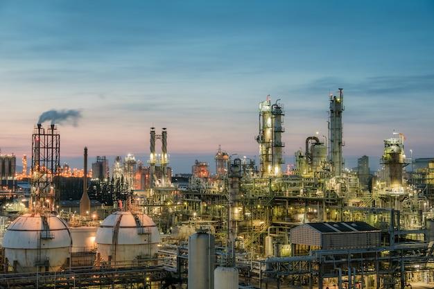 空の夕日を背景に石油およびガス精製プラントまたは石油化学産業、石油産業のガス貯蔵球タンクおよび蒸留塔 Premium写真
