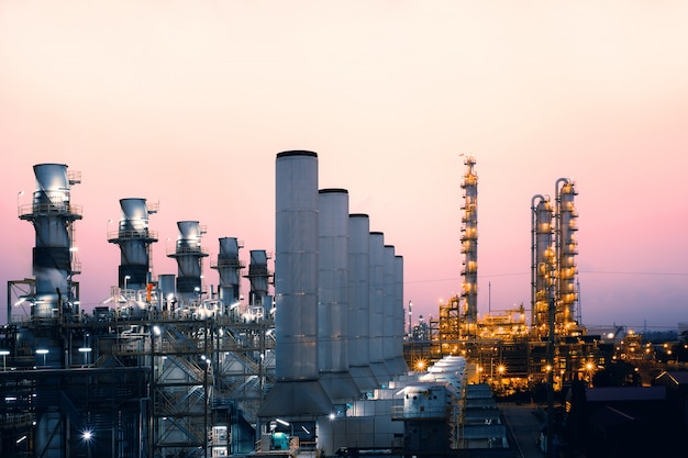 日の出の空の背景、石油化学産業、発電所の煙突のある石油と天然ガスの製油所の工場 Premium写真