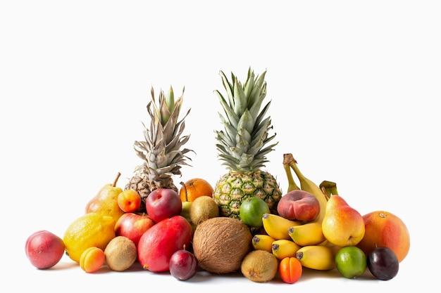 Ассортимент тропических фруктов, изолированные на белом фоне. ананасы, кокос, бананы, манго, яблоки, киви, лайм, лимон, груша, абрикосы, персики и слива. Premium Фотографии