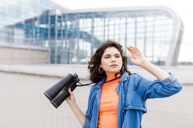Молодая красивая девушка смотрит в сторону с биноклем в руках. Premium Фотографии