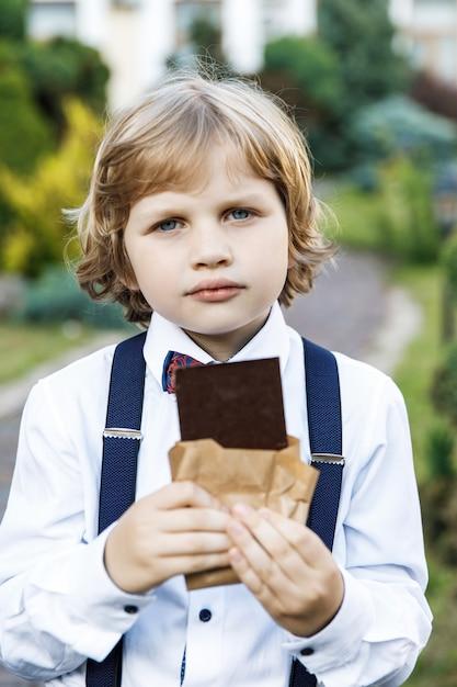 Симпатичный белокурый парень школьных лет одет в школьную форму с удовольствием ест черный шоколад на улице в парке Premium Фотографии