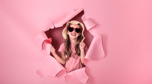 色の壁に棒で心で面白い女の子 Premium写真