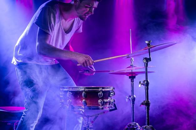 Барабанщик играет на барабанах на синем. красивые спецэффекты света и дыма. процесс игры на музыкальном инструменте. Premium Фотографии