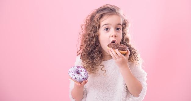 ドーナツを食べる巻き毛少女の肖像画 無料写真