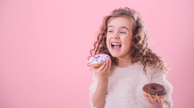 Портрет маленькой кудрявой девочки едят пончики Бесплатные Фотографии