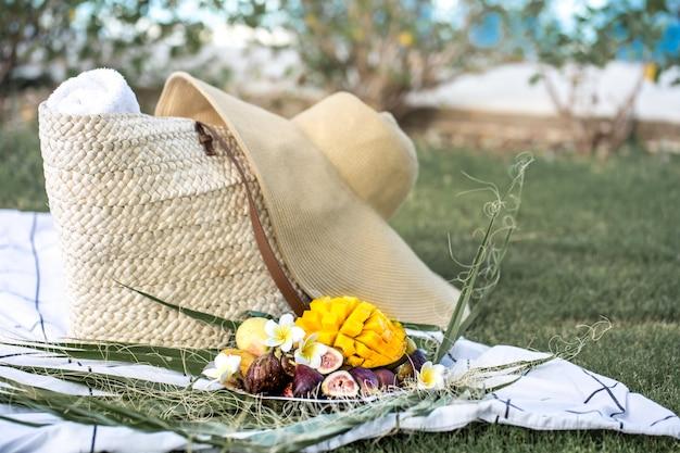 トロピカルフルーツのプレートと夏のピクニック。 無料写真