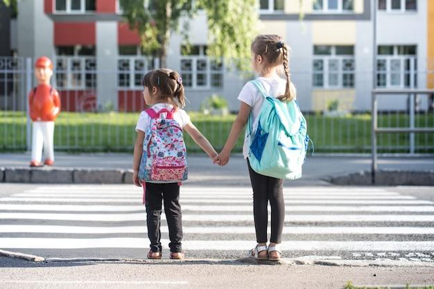 Вернуться к школьному образованию с девочками, учениками начальной школы, с рюкзаками, идущими в класс Premium Фотографии