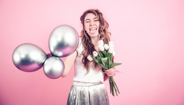Девушка с цветами и шарами на цветной стене Бесплатные Фотографии