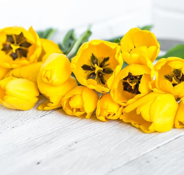 明るい木製の背景に黄色のチューリップの花束 無料写真