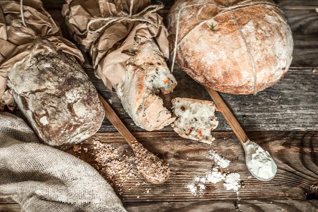 Свежий хлеб и деревянная ложка на старых деревянных фоне Бесплатные Фотографии