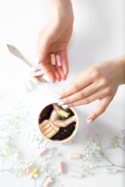 Кофе с маршмеллоу и женскими руками вид сверху Бесплатные Фотографии