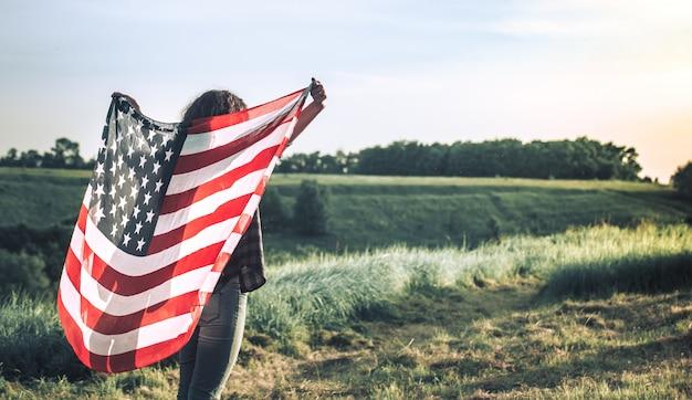 Молодая счастливая девушка работает и прыжки беззаботно с распростертыми объятиями над полем пшеницы. держа флаг сша. Бесплатные Фотографии