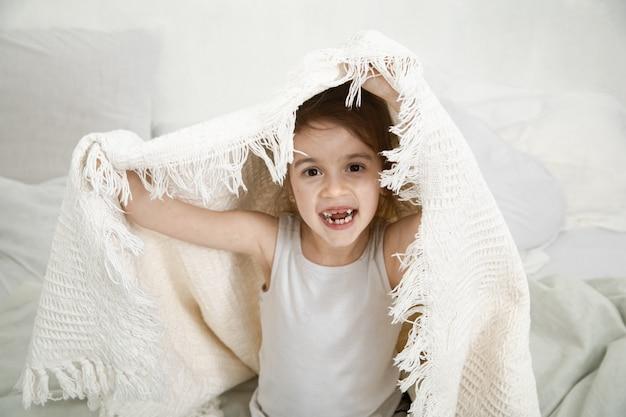 毛布が付いているベッドで遊ぶかわいい女の子。 無料写真