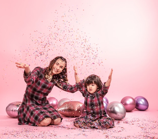 Смешная мама и ребенок, сидя на розовом фоне. маленькая девочка и мать весело с воздушными шарами и конфетти Бесплатные Фотографии