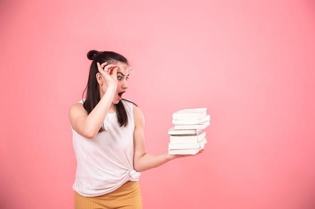 Портрет молодой женщины с очками на розовом фоне с книгами в руках. Бесплатные Фотографии