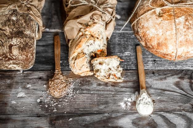 Свежий хлеб и деревянная ложка на старый деревянный стол Premium Фотографии