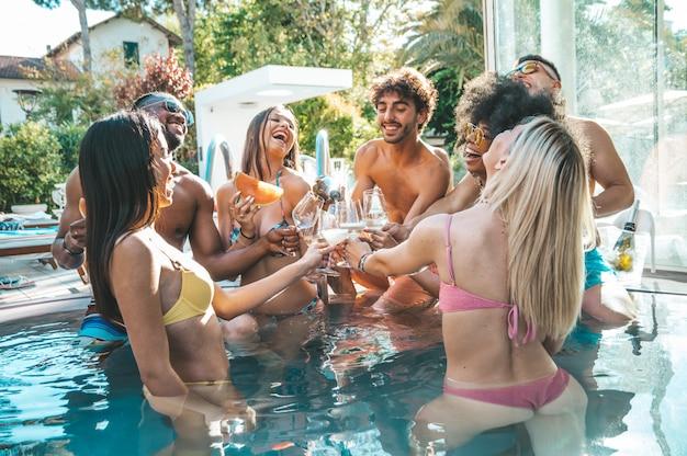 シャンパンで乾杯プールパーティーを作る幸せな友人のグループ。高級リゾートでスパークリングワインを飲みながら笑っている若者。 Premium写真