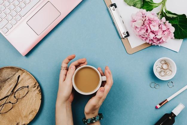 Красивая плоская композиция рабочего стола женщины с розовым ноутбуком, картоном, гортензиями, очками и другими аксессуарами. женский бизнес макет Premium Фотографии