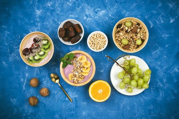 ベリーの植物ベースのヨーグルトボウルのグラノーラ、チア種子、さまざまな果物、青の背景にナッツの健康的なビーガン朝食付きフラットレイ Premium写真