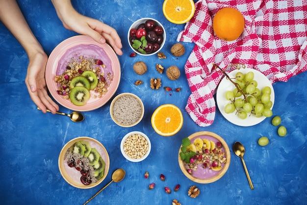 グラノーラ、チアシード、さまざまな果物、青の背景にクルミとベリーの植物ベースのヨーグルトの健康的なビーガン朝食とフラットレイ Premium写真