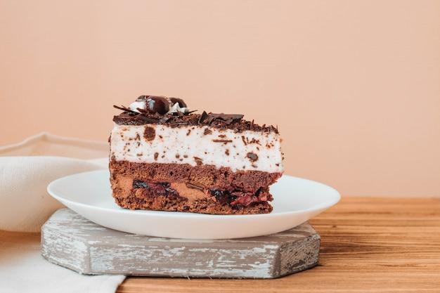 チョコレートとチェリーのケーキ、ベージュの壁の皿の上のケーキ Premium写真